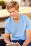 Male High School Student Using Digital Tablet Outdoors. Whilst Sitting Down Smiling Stock Photo