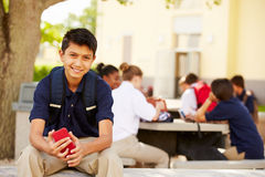 Male High School Student Using Phone On School Campus. Sitting Down Smiling At Camera Royalty Free Stock Photos