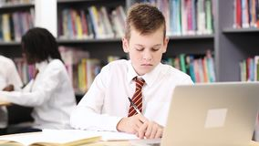 Male high school student wearing uniform working at laptop stock video