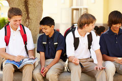 Male High School Students Hanging Out On School Campus. Sitting Down Chatting Royalty Free Stock Photography
