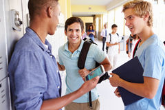 Male High School Students By Lockers Looking At Mobile Phone Royalty Free Stock Photography