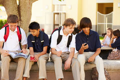 Male High School Students Using Mobile Phones On School Campus Stock Photos