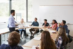 Male High School Tutor With Pupils Sitting At Table Teaching Maths Class stock photo