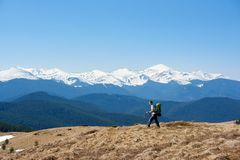 Male hiker with backpack in the mountains. Male hiker with a backpack admiring the view walking on top of the mountain using hiking sticks copyspace achieving Royalty Free Stock Images