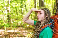 Male hiker with backpack looking at something ahead. In the forest Royalty Free Stock Photography