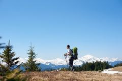 Male hiker with backpack in the mountains. Full length shot of a male hiker with a backpack admiring the view walking on top of the mountain using hiking sticks Stock Images