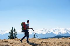 Male hiker with backpack in the mountains. Full length shot of a male hiker with hiking equipment admiring the view walking on top of the mountain using hiking Stock Photos