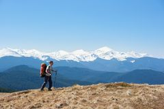 Male hiker with backpack in the mountains. Full length shot of a man tourist with a backpack admiring the view walking on top of the mountain using hiking sticks Stock Photos