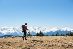 Male hiker with backpack in the mountains. Full length shot of a man tourist with a backpack hiking mountains copyspace landscape view beauty achievement success Stock Photo