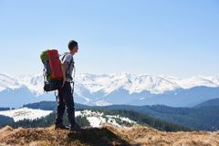 Male hiker with backpack in the mountains. Male hiker with a backpack on his back taking in the view from the top of a mountain copyspace beauty nature landscape Royalty Free Stock Photo