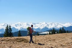 Male hiker with backpack in the mountains. A man hiker with a backpack admiring the view walking in the mountains using hiking sticks copyspace achieving Royalty Free Stock Images