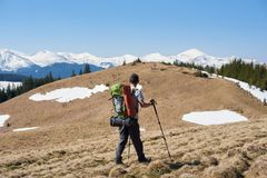Male hiker with backpack in the mountains. Rearview shot of a male hiker with hiking equipment walking in the mountains copyspace sportsman athlete active Stock Images