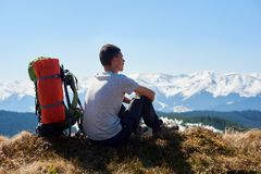 Male hiker with backpack in the mountains. Rearview shot of a male hiker with a backpack sitting on top of the mountain after morning hike admiring the view Royalty Free Stock Image