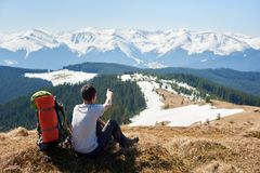 Male hiker with backpack in the mountains. Rearview shot of a male hiker with a backpack sitting on top of a mountain pointing at the snowy mountains far away Royalty Free Stock Photos