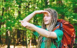 Male hiker with backpack pointing at something ahead. In the forest Stock Image