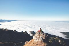 Hiker above clouds. Male hiker with backpack sitting on steep cliff and enjoying stunning view to mountains covered with clouds during autumn day in Bavarian Royalty Free Stock Photography