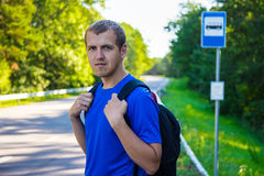 Male hiker with backpack standing on bus stop on forest road. Travel concept - male hiker with backpack standing on bus stop on forest road Stock Image