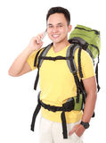 Male hiker with backpack using mobile phone Royalty Free Stock Photo