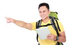 Male hiker with backpack using tablet computer. Portrait of a smiling male hiker pointing to the direction while using tablet computer Royalty Free Stock Photography