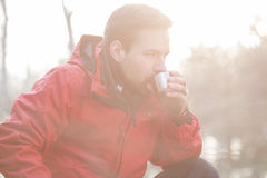 Male hiker drinking coffee in forest Stock Photos