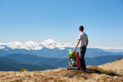Male hiker with backpack in the mountains. Male hiker enjoying morning sun on top of the mountain after a hike copyspace relaxation recreation travelling tourism Stock Photography