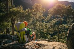 Male hiker enjoying sunset over mountains. Male traveler shot from back sitting on a rock high in the mountains regaining his strength and enjoying sunset in Royalty Free Stock Photos