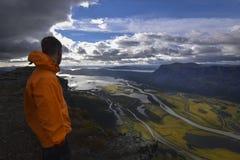 Male hiker enjoying the view over rapadalen river delta in rainy landscape. Sarek, Sweden Stock Image