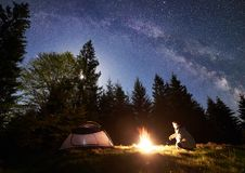 Male hiker enjoyng night camping near tourist tent at campfire under blue starry sky and Milky way. Male backpacker sitting alone near tourist tent at burning stock images