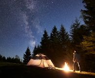 Male hiker enjoyng night camping near tourist tent at campfire under blue starry sky and Milky way. Camping site in mountain valley at night. Silhouette of male royalty free stock photo