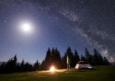 Male hiker enjoyng night camping near tourist tent at campfire under blue starry sky and Milky way. Camping site in mountain valley at night. Male backpacker stock images