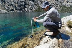 Male hiker filtering drinking water from a turquoise mountain lake. In the Cordillera Blanca in the Andes in Peru Royalty Free Stock Images