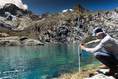 Male hiker filtering drinking water from a turquoise mountain lake. In the Cordillera Blanca in the Andes in Peru Royalty Free Stock Photo