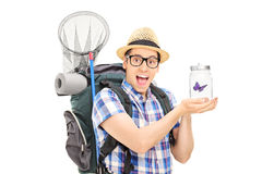 Male hiker holding a butterfly in a jar Royalty Free Stock Photography