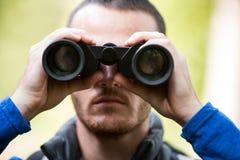 Male hiker looking through binoculars Stock Photos