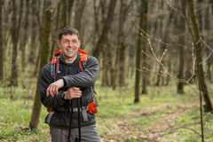 Male hiker looking to the side walking in forest Stock Image