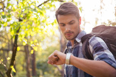 Male hiker looking on wrist watch Royalty Free Stock Photos