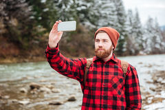Male hiker making photo on smartphone. Outdoors with river on background Stock Photography