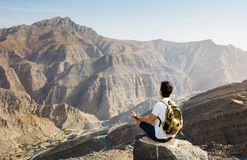Man meditating on the mountain top. Male hiker meditating on the mountain top stock photography