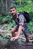 Male hiker in mountain forest. Close-up of male hiker in mountain forest, climbing rocks Stock Image
