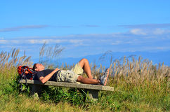 Male Hiker Napping on Bench Stock Images