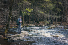 Male Hiker near the edge of a river Stock Photo