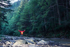 Male hiker with outstretched hands hiking on mountain river. Rear view of male hiker with outstretched hands hiking on mountain river Royalty Free Stock Image