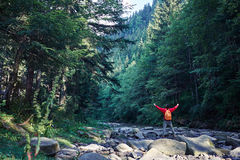 Male hiker with outstretched hands on mountain river. Rear view of male hiker with outstretched hands on mountain river Royalty Free Stock Photos