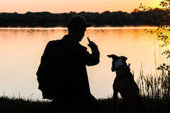Male hiker and pet dog sit near the lake at dawn. Puppy and owner enjoy time near the river at sunset looking in distance Stock Photo