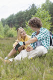 Male hiker pouring coffee for woman while relaxing in field Stock Image