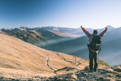 Male hiker relaxing at sunset at the mountain summit and looking at majestic panorama of the italian Alps with dirt road crossing. Colorful meadows in autumn Stock Photography