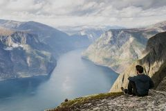 Male hiker relaxing on top of a mountain enjoying the view. Beautiful landscape royalty free stock image