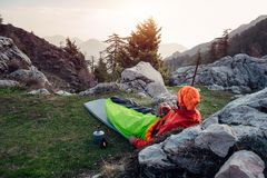 Male hiker rest, drinks coffee and enjoying misty landscape. Hiker sitting on the ground and leaning against the rock enjoys misty morning in Turkey. Shot from Stock Photography