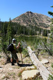 Male hiker by river. Male hiker on a riverside trail stands by a fallen tree trunk Stock Photography