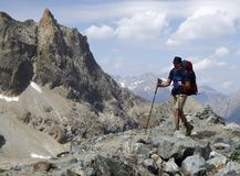 Male hiker on a rocky and dusty hiking trail in the French Alps Royalty Free Stock Photos